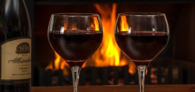 Red wine glasses in front of a fire